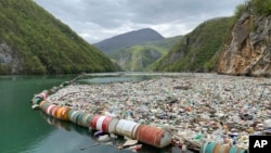 In this photo taken on Tuesday, April 23, 2019, plastic bottles and other garbage float in the river Drina near Visegrad, eastern Bosnia-Herzegovina. (AP Photo/Eldar Emric)