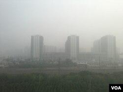 2016年10月14日,北京與河北廊坊交界處霧霾中的樓群。 (美國之音葉兵拍攝)