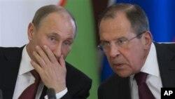El presidente ruso, Vladimir Putin, habla con su canciller, Sergei Lavrov, en una ceremonia este lunes en el Kremlin.
