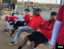 Danish Bashir, center, sits in the dugout at a softball game in Springfield, Virginia. (C. Presutti/VOA)