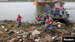 Para petugas kebersihan terus berupaya membersihkan salah satu anak sungai Huangpu di Shanghai dari bangkai babi (10/3). Media setempat mengatakan lebih dari 2.200 bangkai babi ditemukan sungai Huangpu, yang merupakan salah satu sungai sumber air utama di Shanghai. Hal ini memicu kecemasan warga akan keamanan pangan dan polusi lingkungan di wilayah itu.