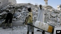 Seorang pria Palestina berbicara dengan seorang anak di antara reruntuhan Masjid al-Qassam, di kamp pengungsi Nusseirat, Jalur Gaza (10/8).