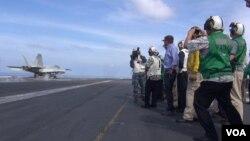 美國國防部長卡特(穿藍衣者)在約翰·C斯坦尼斯號航空母艦上觀看戰機起飛。
