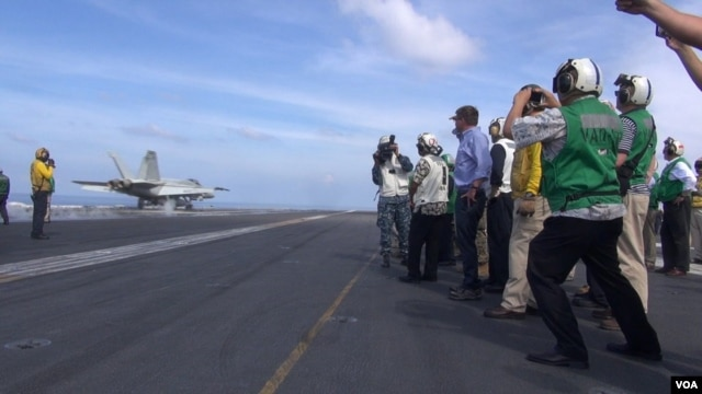 U.S. Secretary of Defense Ash Carter (center, in blue shirt) watches a jet take off from the USS John C. Stennis in the South China Sea (C.Babb/VOA). Carter says the U.S. is strengthening its military role in the region but is not aiming to provoke anything.