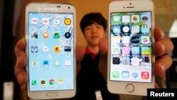Seorang pegawai toko di Seoul memegang ponsel Samsung Electronics edisi Galaxy 5 (kiri) dan Apple Inc seri iPhone 5. (Foto: Dok)