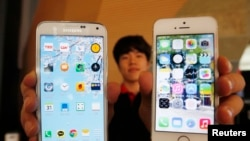 FILE - Sales associate displays Samsung Electronics' Galaxy 5 smartphone, left, and Apple Inc.'s iPhone 5 in Seoul, July 16, 2014.