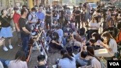 大批傳媒在支聯會舉行特別會員大會的六四紀念館所在的大廈出入口外,訪問支聯會公司秘書蔡耀昌,談支聯會清盤解散的安排。(美國之音湯惠芸)