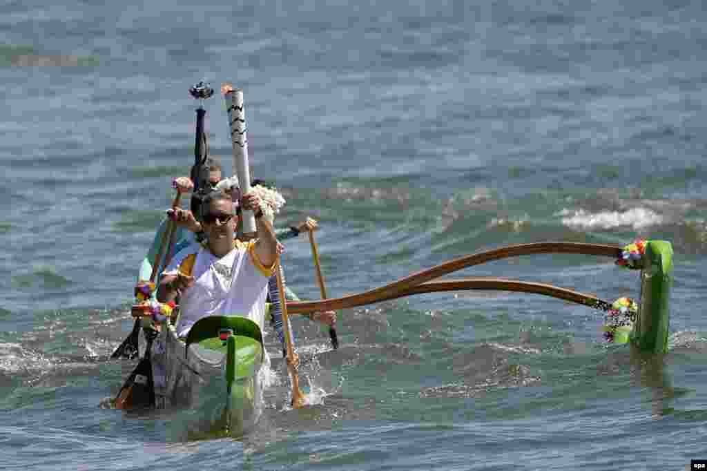Brazilian canoeist Rubens Pompeu carries the Olympic flame during a tour through Paranoa lake in Brasilia, Brazil. The Olympic flame arrived to Brazil kicking off a three-month torch relay throughout the country that will finish at the Maracana stadium on Aug. 5, 2016, with the opening ceremony of the Rio 2016 Olympic Games.