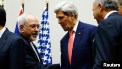 FILE - U.S. Secretary of State John Kerry, right, shakes hands with Iranian Foreign Minister Mohammad Javad Zarif, United Nations, Geneva, Nov. 24, 2013.