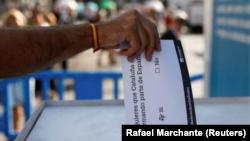 En la imagen, un hombre introduce una papeleta en una urna durante el referéndum de independencia del 1 de octubre de 2017.