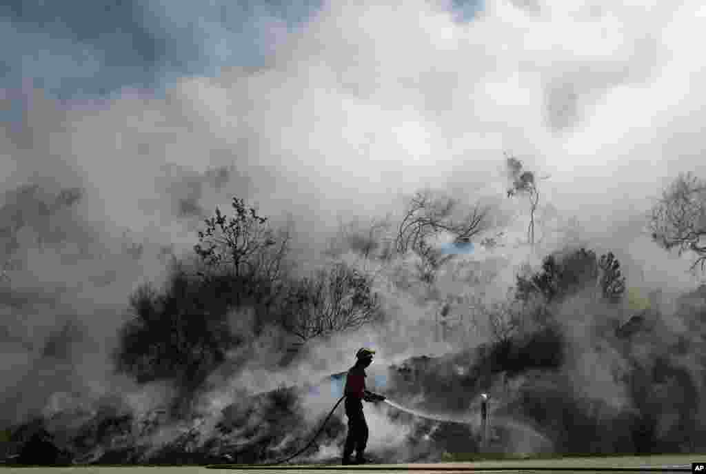 A Portuguese firefighter fights to extinguish a fire in Adsamo, near Vouzela, Portugal. More than 600 firefighters were battling six new wildfires a day after one firefighter was killed and nine others injured when gusting winds winds caused a fire to change direction.