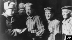 FILE- In this file photo dated January 1945, three prisoners, right, talk with Soviet soldiers after the Nazi concentration camp Auschwitz, in Poland, was liberated.