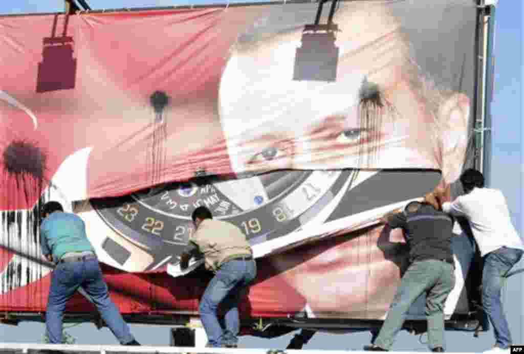 Lebanese men of Armenian descent, tear up a poster showing Turkish Prime Minister Recep Tayyip Erdogan as they protest against his visit, in Beirut's Martyrs' Square, Lebanon, Thursday, Nov. 25, 2010. (AP Photo/Assad Ahmad)