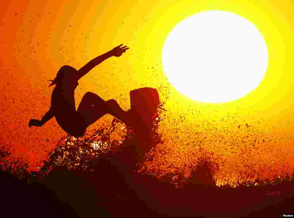 Surfer Cole Clisby rides his surfboard off the top of a wave as the sun sets off the shores of Leucadia, California, Jan. 15, 2014.
