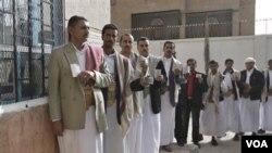 Para calon pemilih antri di depan sebuah TPS di Sanaa, Yaman (21/2).