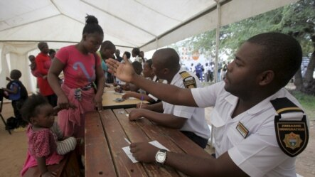 FILE: Refugees fleeing anti-immigrant violence are processed by immigration officers at a transit camp in Beit Bridge, ZImbabwe, April 24, 2015.