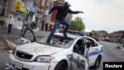 Demonstrators jump on a damaged Baltimore police department vehicle during clashes in Baltimore, Maryland, April 27, 2015.