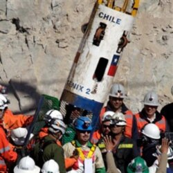 Miner Edison Pena, center, emerging from the capsule that brought him to the surface from the collapsed mine near Copiapo, Chile