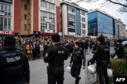 Turkish anti-riot police officers stand guard as people gather outside Bakirkoy courthouse in Istanbul, Jan. 12, 2018, in support of the jailed co-chair of the People's Democratic Party (HDP).