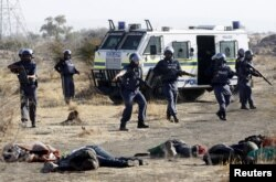 FILE - A policeman gestures in front miners after they were shot dead outside a South African mine in Rustenburg, 100 km (62 miles) northwest of Johannesburg, Aug. 16, 2012.