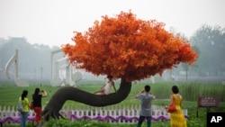 """在北京郊区的雾霾中,游客在""""希望树""""旁照相。许多人希望中国改善环境,消除雾霾"""