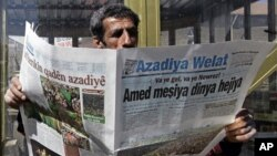 A man reads a Kurdish newspaper in southeastern city of Diyarbakir, Turkey, March 22, 2009.