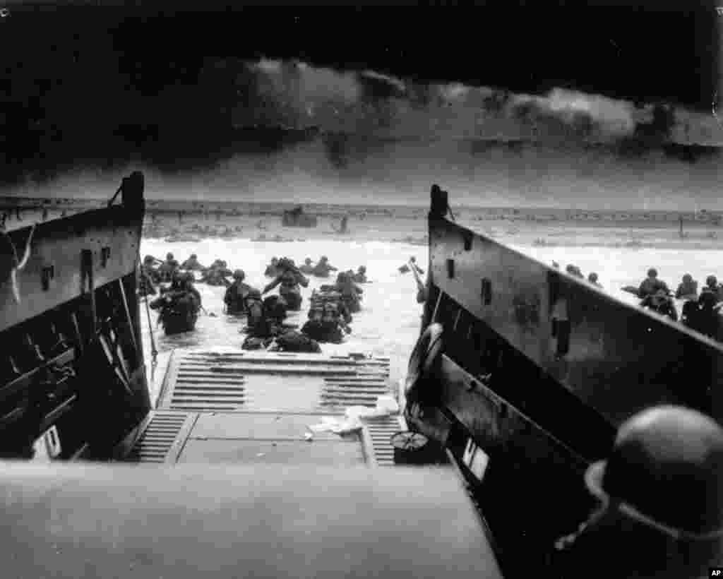 While under heavy machine gun fire from the German coastal defense forces, American soldiers maneuver off the ramp of a U.S. Coast Guard landing craft during the Allied landing operations at Normandy, France, June 6, 1944.