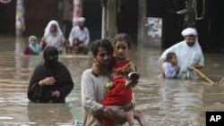 تعدادی از شهروندان پاکستان که در میان آب ناشی از سیل منازل شانرا ترک نموده اند.