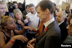 The British Ambassador to Egypt, John Casson, talks to British tourists after the announcement by easyJet staff that there would not be any more flights today to evacuate tourists from Sharm el-Sheikh, south Sinai, Egypt, Nov. 6, 2015.