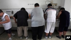 FILE - In this July 24, 2008 file photo, obese patients wash their plates after lunch at the Aimin Fat Reduction Hospital in Tianjin, China.