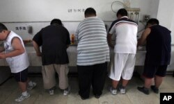 FILE - In this July 24, 2008, file photo, obese patients wash their plates after lunch at the Aimin Fat Reduction Hospital in Tianjin, China. A study released at that time said China had surpassed some richer countries long plagued with diabetes to develop the world's biggest epidemic.