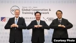"""外交部长吴钊燮(中)与美国在台协会台北办事处(AIT)处长郦英杰(Brent Christensen,左)及日本台湾交流协会台北事务所代表泉裕泰(Hiroyasu Izumi,右)于6月1日的""""全球合作暨训练架构(GCTF)""""5周年记者会上拱手合影。(台湾外交部提供)"""