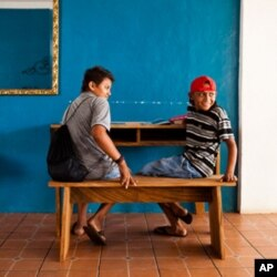 Students in El Cuco, El Salvador, try out a bench and desk made by Surf for Life members Danny Hess and Jay Nelson.