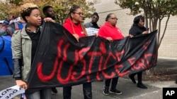"""Para pengunjuk rasa mengangkat poster yang berbunyi """"Keadilan untuk E.J."""" selama unjuk rasa yang berlangsung di Riverchase Galleria di Hoover, Alabama, Sabtu, 24 November 2018 (foto: AP Photo/Kim Chandler)"""