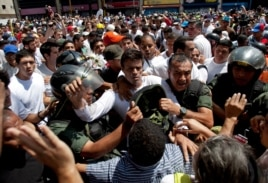 Opposition leader Leopoldo Lopez, dressed in white and holding up a flower stem, is taken into custody by Bolivarian National Guards, in Caracas, Venezuela, Feb 18, 2014.