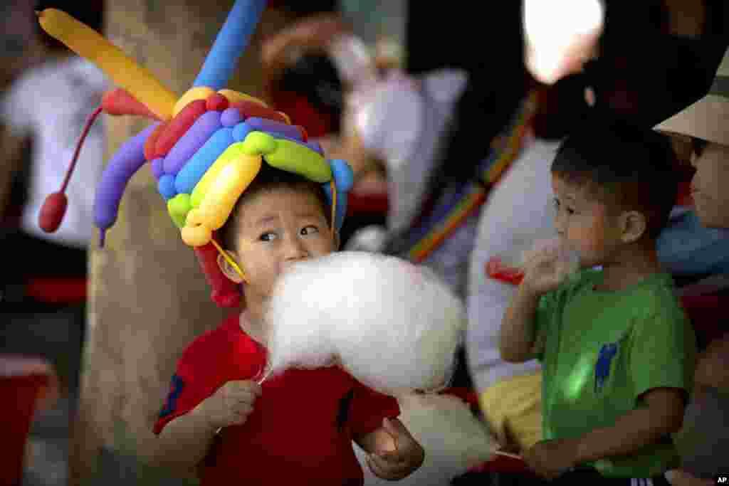 2017年6月1日,在北京的一个公园里,一名男孩戴着气球帽子,吃棉花糖。全世界许多国家庆祝国际儿童节。