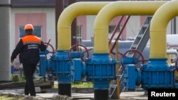 An employee walks past gas pipes at Oparivske gas underground storage in the Lviv region, Ukraine, Sept. 30, 2014.