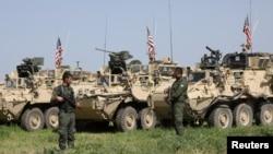 کرد فوج کے اہل کار امریکی فوجی گاڑیوں کے قریب کھڑے ہیں۔ فائل فوٹو