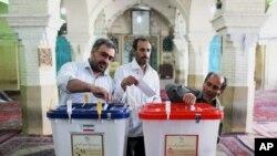 Warga Iran memasukkan surat suaranya ke dalam kotak suara di salah satu TPS di Qom, 125 kilometer sebelah utara ibukota Teheran, Iran (14/6).