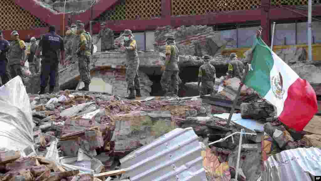 Des soldats enlèvent des débris dans un bâtiment municipal partiellement effondré après le tremblement de terre à Juchitan, au Mexique, le 8 septembre 2017.