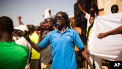 FILE - A man shouts as he and others gather at the Place de Nation calling for a civilian democratic transition in Ouagadougou, Burkina Faso, Nov. 2, 2014.