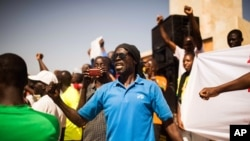 FILE - A man shouts as he and others are seen gathered at the Place de Nation calling for a civilian democratic transition in Ouagadougou, Burkina Faso, Nov. 2, 2014.