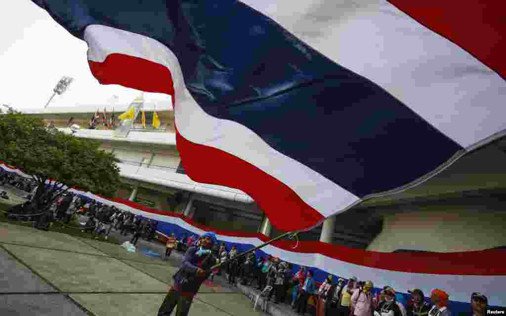 An anti-government protester waves a Thai national flag at the gymnasium where candidates register for upcoming elections in Bangkok, Dec. 25, 2013.