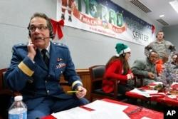 Brigjen Guy Hamel asal Kanada, wakil direktur kebijakan, strategi dan perencanaan NORAD dan USNORTHCOM, turut membantu para relawan menjawab telepon anak-anak dari seluruh dunia yang ingin tahu kapan Sinterklas akan mampir membawa hadiah, dari sebuah pusat panggilan telepon di Colorado, 24 Desember 2014. (Foto:Dok)