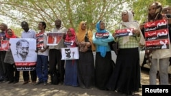 Journalists carry signs demanding freedom of press and expression during a demonstration against the violations of the security services towards the press and journalists outside the Council of the Press and Publication, in Khartoum, Sudan, May 16, 2012.