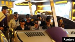 "Staff members wearing virtual reality goggles sit in a motorized cart while performing an inspection of the attraction ""Fly Over Guizhou,"" at the Oriental Science Fiction Valley theme park in Guiyang, Guizhou province, China, Nov. 16, 2017."