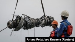 Rescue team members lift up a turbine engine of Lion Air flight JT610 at the north coats of Karawang, Indonesia, Nov. 3, 2018.