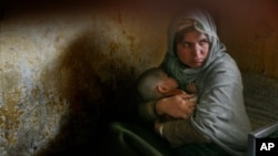 Habiba, who has completed three years of a 10-year prison sentence for murder, holds her daughter Nazanin who was born in jail three years ago but still cannot walk, as they rest in their bunk bed inside Pul-e Charkhi prison in Kabul, Afghanistan. (File P