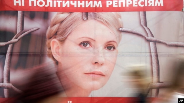 "People pass by a poster of Ukraine's imprisoned former prime minister Yulia Tymoshenko at a tent camp of her supporters in central Kyiv, Ukraine, in this April 30, 2013, file photo. The text on top reads: ""No to political repressions."""