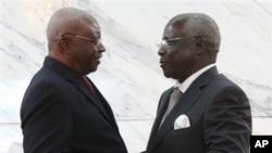 Dans cette photo d'archive datée du vendredi 5 septembre 2014, le président du Mozambique Arnando Guebuza, à gauche, et l'ancien chef rebelle Renamo Afonso Dhlakama, se serrent la main après la signature d'un accord de paix à Maputo, au Mozambique.